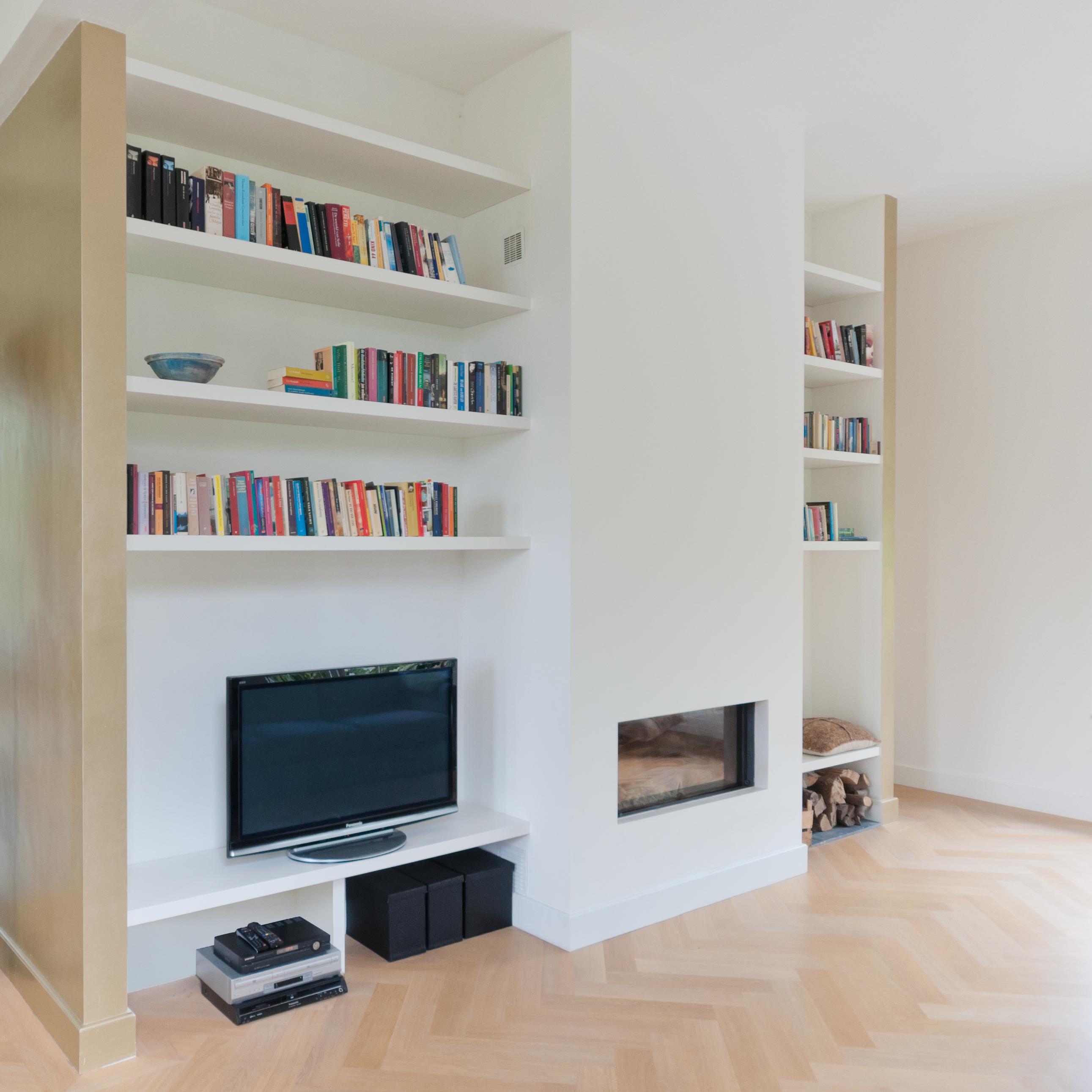 Inbouwkast voor open haard, gecombineerd met zwevende boekenplanken. De boekenplanken zijn onzichtbaar gemonteerd en iedere kleur te leveren.
