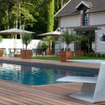 Terrasopbouw om een zwembad op maat gemaakt. Het terras bestaat uit houten delen gemaakt van tropisch hardhout. De plantenbakken zijn tevens op maat gemaakt.